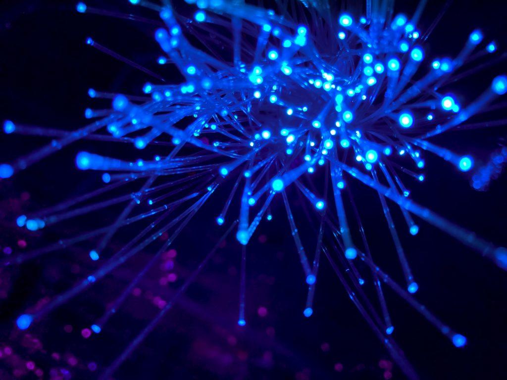 Illustration med blå självlysande trådar mot en mörk bakgrund