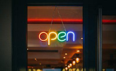 Foto av en dörr med en neonskylt som visa ordet Open på engelska